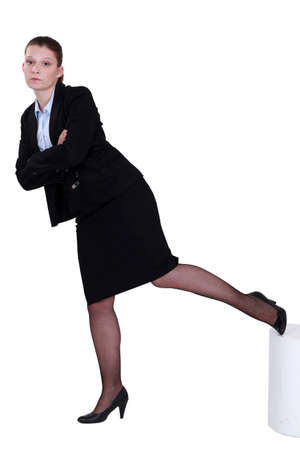 Stern businesswoman standing on one leg Stock Photo - 13375559