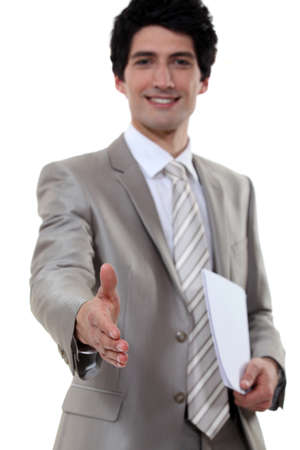 young businessman all smiles shaking hands with invisible businesspartner photo
