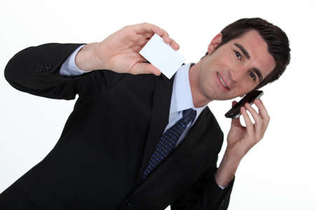 personalised: Businessman talking on his mobile phone and holding a card Stock Photo