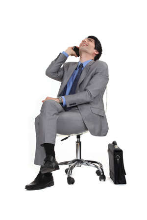 executive affable: Man sitting in a chair by phone Stock Photo