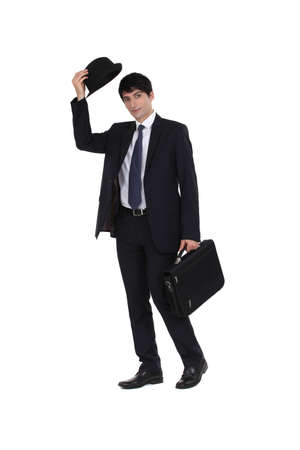 greet: smart young businessman with suitcase greeting by removing bowler