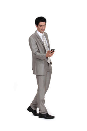 Young businessman sending text message whilst walking photo