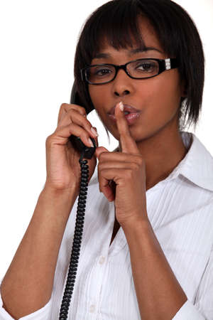 Woman talking on the phone and holding her finger to her lips photo