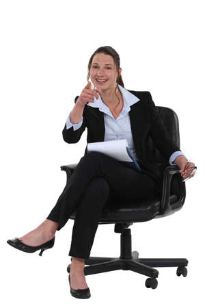 young businesswoman sitting in a chair and pointing at you photo