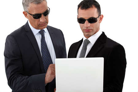 Serious men in smart suits with sunglasses holding a laptop photo