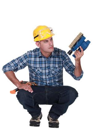 en cuclillas: Hombre con una lijadora eléctrica