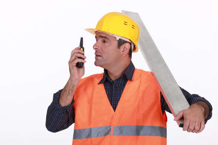 Labourer speaking into a walkie-talkie photo