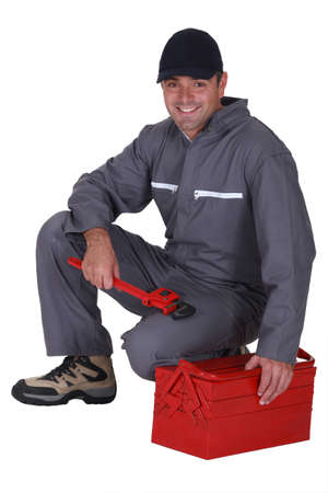 installer: Worker sitting on a toolbox Stock Photo
