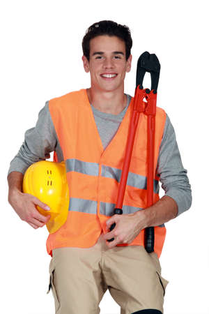 two and two thirds: Worker in a reflective vest with helmet and boltcutters