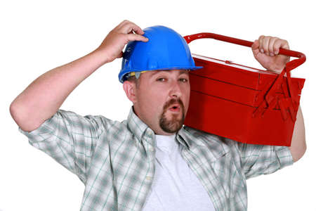 man carrying box: Man carrying tool box on shoulders