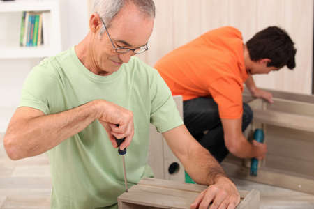 self help: Father and son putting together flatpack furniture Stock Photo