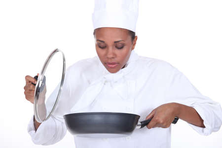 Female chef looking in a pan of food photo