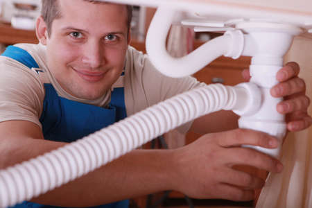 Plumber fitting a kitchen sink photo