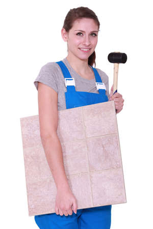 jumpsuite: young woman holding tiles an a hammer Stock Photo