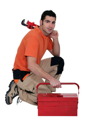Labourer kneeling by tool box Stock Photo