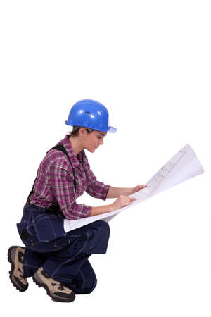 Female builder looking at architect plans photo