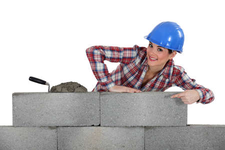 unbiased: portrait of young female bricklayer pointing at concrete wall Stock Photo