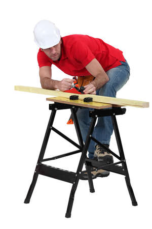 whittle: Man planning plank of wood Stock Photo