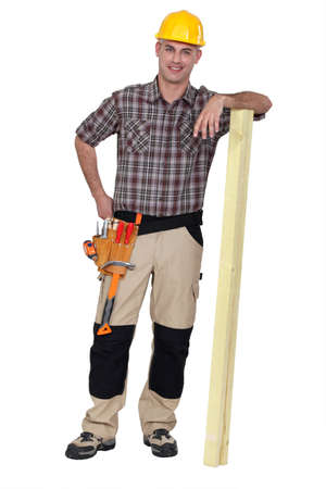 Carpenter stood with plank of wood Stock Photo