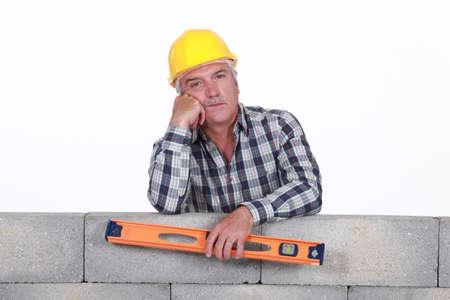 stonemasonry: Bored tradesman holding a spirit level