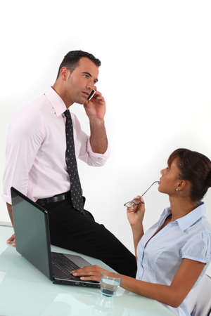 Businessman on the phone and businesswoman sitting at a desk photo