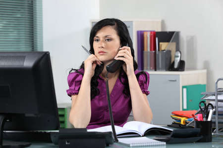 Beautiful young woman working in office photo