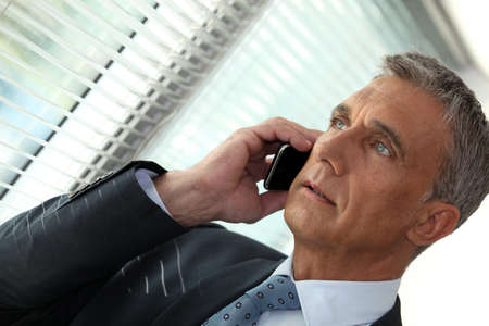 55 60 years: Businessman on the phone looking out of an office window