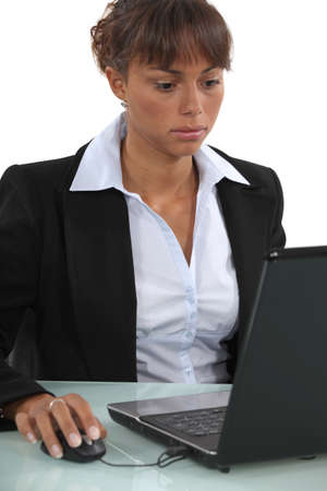 long faced: long-faced businesswoman working on laptop Stock Photo