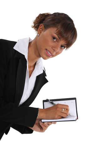 Woman writing in her agenda Stock Photo - 13460256