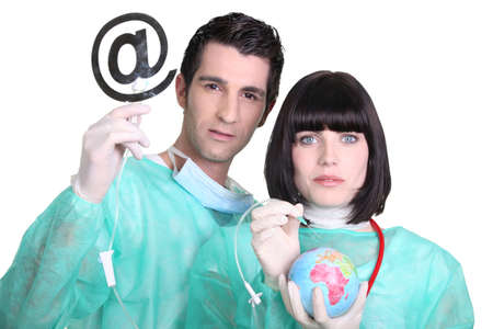 lab coat: Medical professionals with at sign and globe Stock Photo
