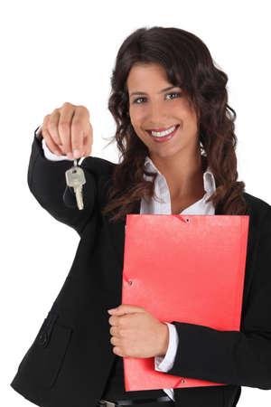 handover: Female estate-agent holding keys and folder