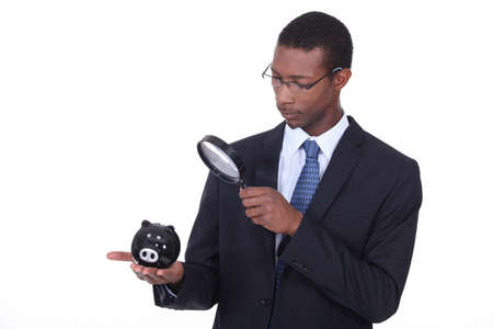 american banker: Man examining piggy bank with a magnifying glass Stock Photo
