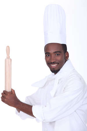 young black male cook is taking a rolling pin like a base-ball player