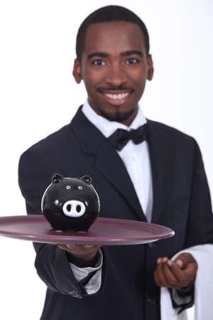 Waitor holding piggy bank photo