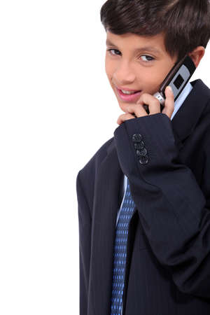 Little boy wearing a business suit and chatting on a cellphone photo