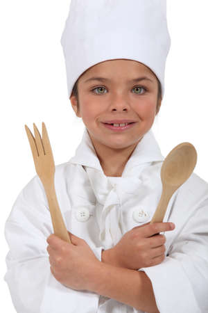 teenage girl dressed in cook costume holding wooden spoon and fork