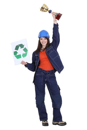 Female builder holding trophy and recycling logo photo
