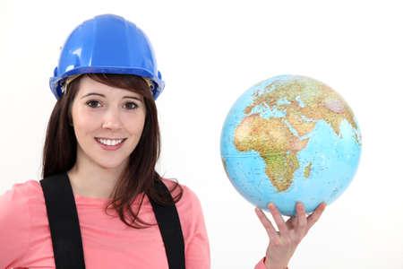 Female builder holding globe Stock Photo - 13459469