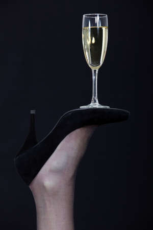 шик: Шампанское стекло балансирует на подошве обуви