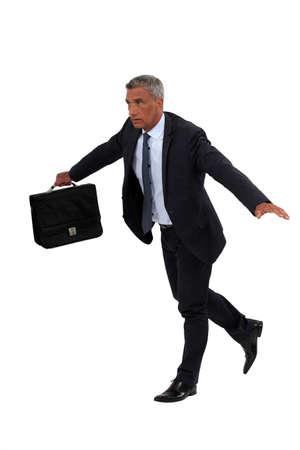 to tight: Senior businessman walking on a tight-rope Stock Photo