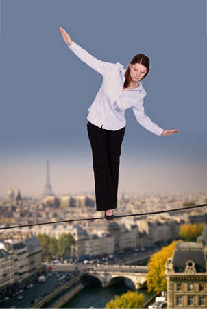 tightrope: Businesswoman walking along tight rope Stock Photo
