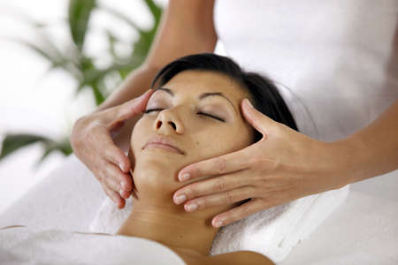 Masseuse giving face massage photo