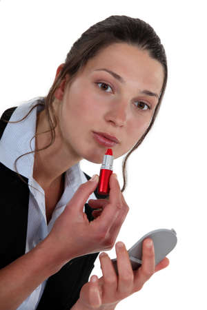 A businesswoman putting red lipstick on  photo