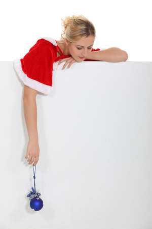 disguised: Woman with Christmas coat and blue ball Stock Photo