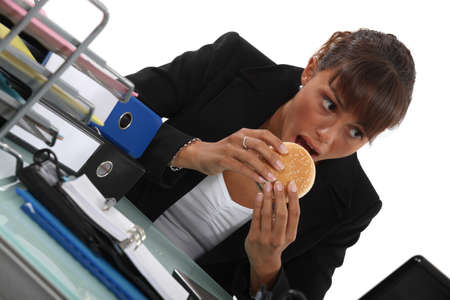 Woman eating burger at desk photo