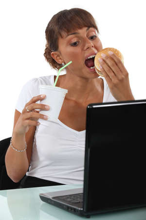 Woman eating a burger at her desk Stock Photo - 13459475