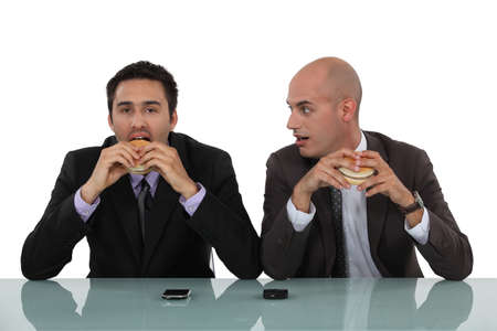 Businessmen eating burgers photo