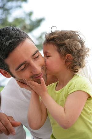 little girl kissing her father photo