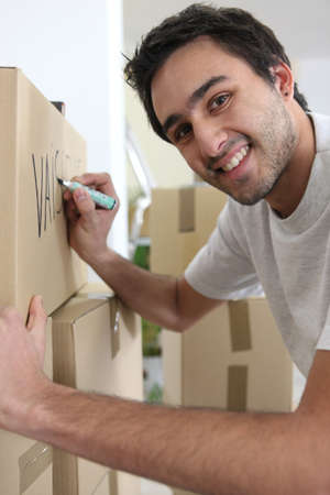 Young man writing on moving boxes Stock Photo - 13459035