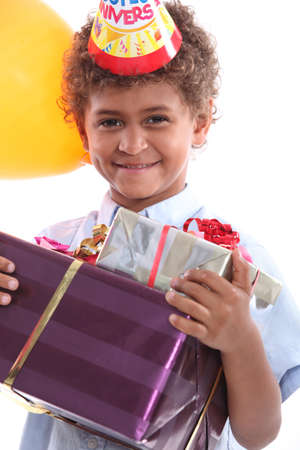 a little boy holding a conical hat and birthday gifts in his arms photo